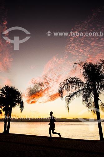 Pessoa correndo no calçadão da Avenida Beira Mar Norte durante o pôr do sol  - Florianópolis - Santa Catarina (SC) - Brasil