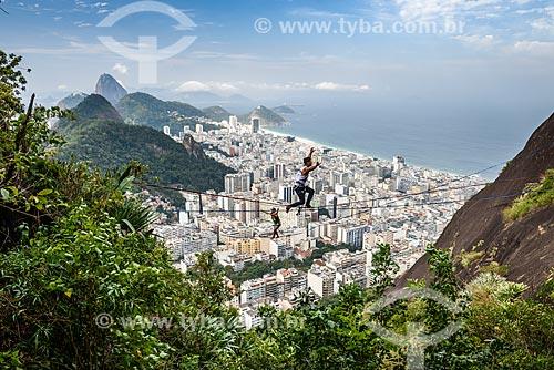 Praticante de slackline no Morro dos Cabritos com o bairro de Copacabana e o Pão de Açúcar ao fundo  - Rio de Janeiro - Rio de Janeiro (RJ) - Brasil