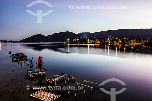 Silhueta de casal sobre trapiche na Lagoa da Conceição ao anoitecer  - Florianópolis - Santa Catarina (SC) - Brasil