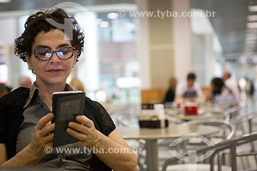 Mulher com telefone celular na praça de alimentação do Aeroporto Santos Dumont  - Rio de Janeiro - Rio de Janeiro (RJ) - Brasil