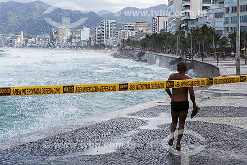 Banhista no calçadão da Praia do Arpoador durante ressaca com faixa de interdição  - Rio de Janeiro - Rio de Janeiro (RJ) - Brasil