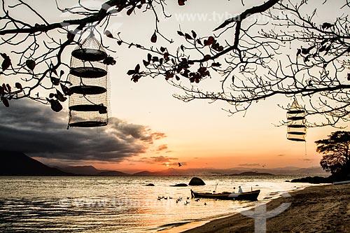 Silhueta de barco e pescador na Praia da Tapera ao pôr do sol  - Florianópolis - Santa Catarina (SC) - Brasil