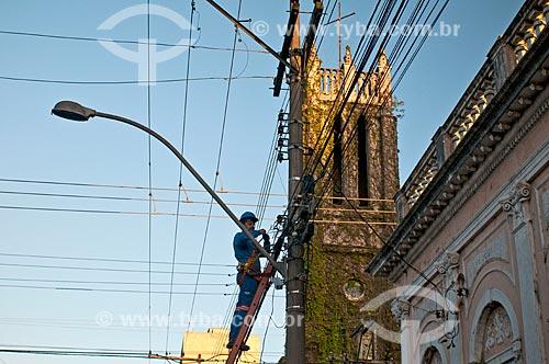 Operário fazendo manutenção na rede telefônica com a Catedral Anglicana do Redentor (1892) - também conhecida como Igreja Cabeluda - ao fundo  - Pelotas - Rio Grande do Sul (RS) - Brasil