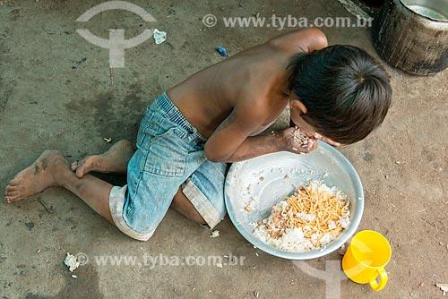 Criança comendo com a mão no pátio da Aldeia Moikarakô - Terra Indígena Kayapó  - São Félix do Xingu - Pará (PA) - Brasil