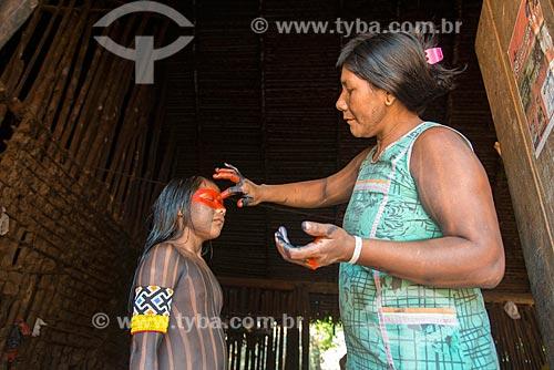 Mãe fazendo pintura corporal em menina na Aldeia Moikarakô - Terra Indígena Kayapó  - São Félix do Xingu - Pará (PA) - Brasil