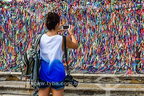 Mulher fotografando as fitinhas coloridas nas grades da Igreja de Nosso Senhor do Bonfim (1754)  - Salvador - Bahia (BA) - Brasil