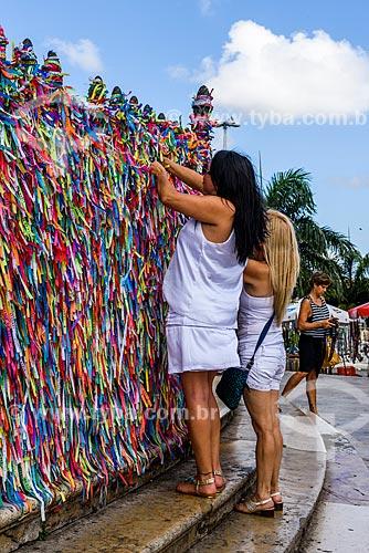 Mulhers amarrando fitinhas coloridas nas grades da Igreja de Nosso Senhor do Bonfim (1754)  - Salvador - Bahia (BA) - Brasil