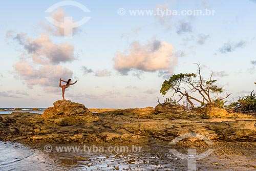 Mulher praticando Yoga na orla entre a 3ª Praia e 4ª Praia - movimento Dandayamana-dhanurasana  - Cairu - Bahia (BA) - Brasil