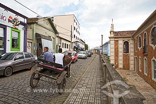 Carroça na Rua Capitão João Rocha com Igreja de Nossa Senhora do Monte Serrat (1754) à direita  - Baependi - Minas Gerais (MG) - Brasil
