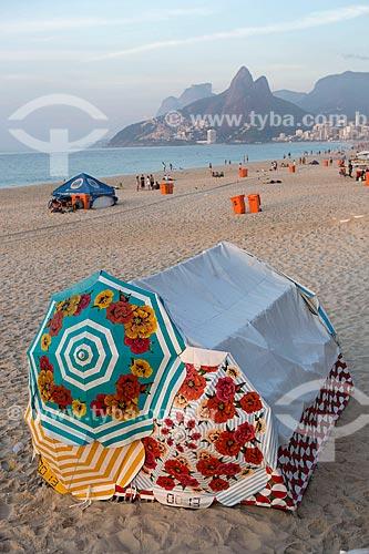 Barraca de camping protegida com três guarda-sóis coloridos na Praia de Ipanema - porto 8 - após festa de Réveillon  - Rio de Janeiro - Rio de Janeiro (RJ) - Brasil