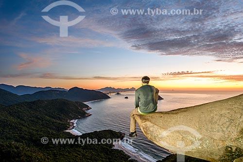 Homem observando o litoral do Rio de Janeiro a partir da Pedra do Telégrafo no Morro de Guaratiba durante o amanhecer  - Rio de Janeiro - Rio de Janeiro (RJ) - Brasil