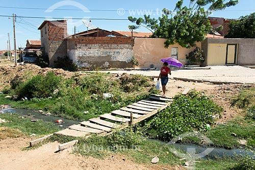Mulher atravessando ponte de madeira sob esgoto a céu aberto na periferia de Cabrobó  - Cabrobó - Pernambuco (PE) - Brasil