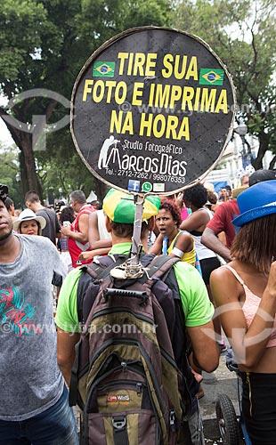 Fotógrafo com placa oferecendo os seus serviços durante o desfile do bloco de carnaval de rua Cordão do Bola Preta  - Rio de Janeiro - Rio de Janeiro (RJ) - Brasil