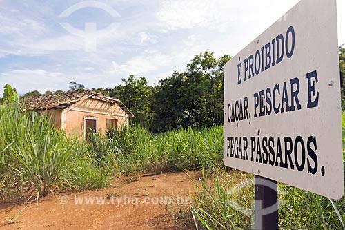 Placa que diz: É proibido caçar, pescar e pegar pássaros - na zona rural da cidade de Guarani com casa abandona ao fundo  - Guarani - Minas Gerais (MG) - Brasil