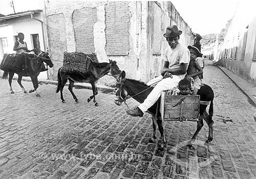 Caixeiro-viajante carregando criança em bruaca -  bolsa feita de couro  - Cachoeira - Bahia (BA) - Brasil
