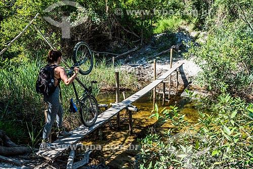 Mulher atravessando ponte de madeira no Parque Nacional da Serra do Cipó  - Santana do Riacho - Minas Gerais (MG) - Brasil