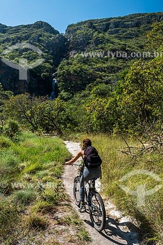 Mulher andando de bicicleta no Parque Nacional da Serra do Cipó com a Cachoeira da Farofa ao fundo  - Santana do Riacho - Minas Gerais (MG) - Brasil