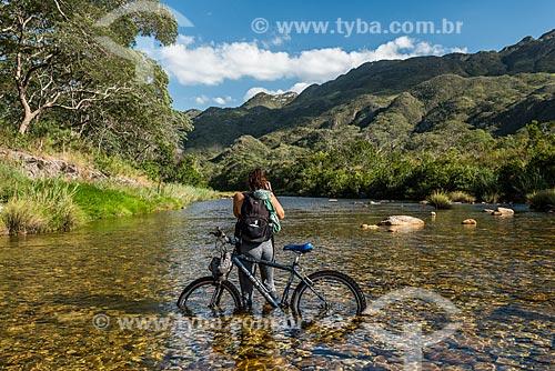 Ciclista cruzando e fotografando o Rio Mascates no Parque Nacional da Serra do Cipó  - Santana do Riacho - Minas Gerais (MG) - Brasil