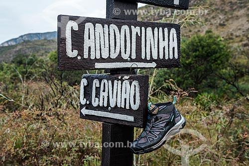 Detalhe de tênis secado em placa de trilha no Parque Nacional da Serra do Cipó indicando as direções para as Cachoeira das Andorinhas (à direita) e Cachoeira do Gavião (à esquerda)  - Jaboticatubas - Minas Gerais (MG) - Brasil