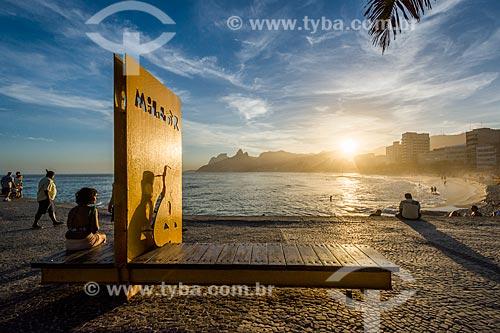 Mulher sentada no monumento à Millôr Fernandes no Largo do Millôr durante o pôr do sol na Praia do Arpoador  - Rio de Janeiro - Rio de Janeiro (RJ) - Brasil