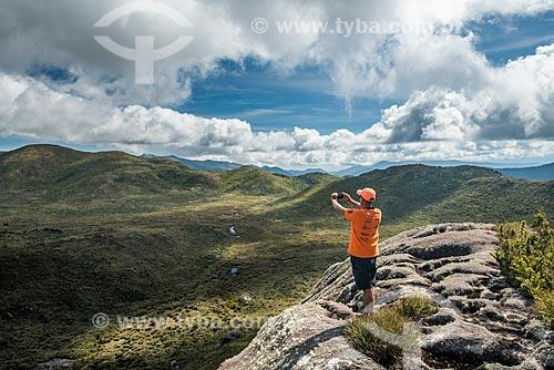 Homem fotografando a paisagem a partir da trilha na Serra da Mantiqueira no Parque Nacional de Itatiaia com o Rio Aiuruoca ao fundo  - Itatiaia - Rio de Janeiro (RJ) - Brasil