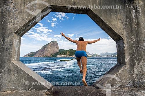 Homem saltando na Baía de Guanabara a partir da passarela do Forte Tamandaré da Laje (1555) com o Pão de Açúcar ao fundo  - Rio de Janeiro - Rio de Janeiro (RJ) - Brasil