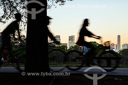 Silhueta de pessoas andando de bicicleta no Parque do Ibirapuera com o Monumento aos heróis de 32 (1965) ao fundo  - São Paulo - São Paulo (SP) - Brasil