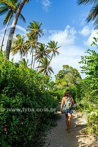 Mulher em trilha de acesso à Praia de Moreré  - Cairu - Bahia (BA) - Brasil