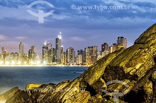 Vista do pôr do sol a partir do rochedo da Praia da Barra Norte com os prédios da Avenida Atlântica ao fundo  - Balneário Camboriú - Santa Catarina (SC) - Brasil