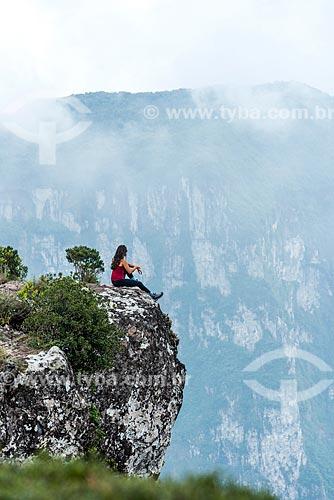 Mulher sentada em uma pedra na beira do Cânion Fortaleza no Parque Nacional dos Aparados da Serra  - Cambará do Sul - Rio Grande do Sul (RS) - Brasil