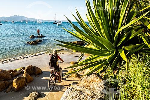Pescador e ciclista na orla da Praia de Jurerê  - Florianópolis - Santa Catarina (SC) - Brasil