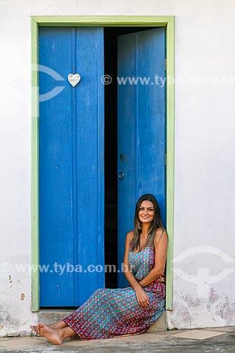 Detalhe de jovem mulher sentada em frente à porta  - Guarani - Minas Gerais (MG) - Brasil