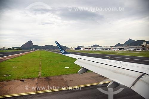 Vista da asa de avião na pista do Aeroporto Santos Dumont com o Pão de Açúcar ao fundo  - Rio de Janeiro - Rio de Janeiro (RJ) - Brasil