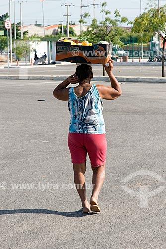 Mulher carregando frutas descartadas na cabeça na Centrais de Abastecimento do Ceará S.A. - CEASA do Cariri  - Barbalha - Ceará (CE) - Brasil