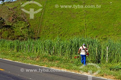 Homem podando grama acostamento do Rodovia MG-353 entre as cidades de Guarani e Pirauba  - Guarani - Minas Gerais (MG) - Brasil