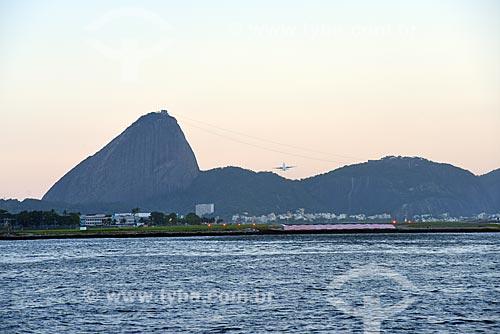 Vista de avião decolando do Aeroporto Santos Dumont durante o Rio Boulevard Tour - passeio turístico de barco na Baía de Guanabara - com o Pão de Açúcar ao fundo  - Rio de Janeiro - Rio de Janeiro (RJ) - Brasil