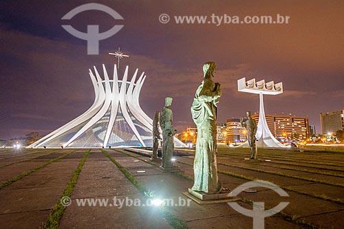 Escultura Os Evangelistas com o Catedral Metropolitana de Nossa Senhora Aparecida (1958) - também conhecida como Catedral de Brasília - durante a noite  - Brasília - Distrito Federal (DF) - Brasil