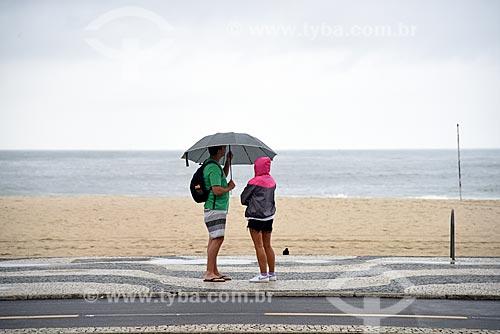 Casal na orla da Praia de Copacabana durante a chuva  - Rio de Janeiro - Rio de Janeiro (RJ) - Brasil