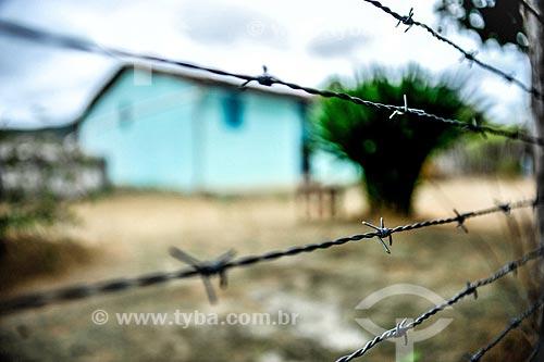 Detalhe de cerca de arame farpado com casa ao fundo  - Jacobina - Bahia (BA) - Brasil