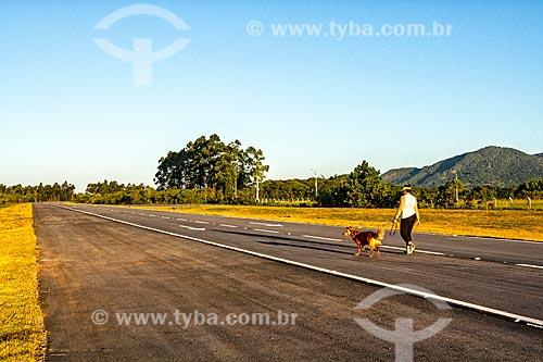 Mulher passeando com cachorro no trecho do novo acesso ao terminal de passageiros do Aeroporto Internacional de Florianópolis - Hercílio Luz  - Florianópolis - Santa Catarina (SC) - Brasil