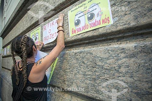 Mulher colando cartaz durante manifestação em frente à Palácio Pedro Ernesto (1923) - sede da Câmara Municipal do Rio de Janeiro - contra a reforma da previdência do Rio de Janeiro  - Rio de Janeiro - Rio de Janeiro (RJ) - Brasil