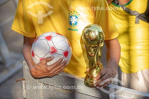 Detalhe de torcedor segurando bola e réplica do Troféu da Copa do Mundo da FIFA no Boulevard Olímpico durante o jogo entre Brasil x Bélgica pela Copa do Mundo 2018 - jogo em que o Brasil foi eliminado  - Rio de Janeiro - Rio de Janeiro (RJ) - Brasil