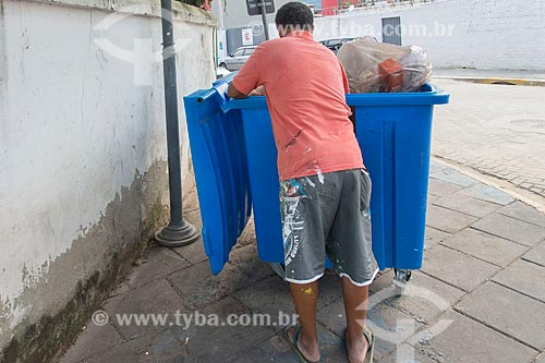 Catador de papelão procurando objetos em lixeira  - São Sebastião - São Paulo (SP) - Brasil