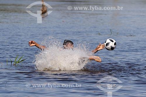 Menino ribeirinho brincando com a Adidas Telstar - bola de futebol oficial da Copa do Mundo FIFA de 2018 - no Igarapé Açu  - Manacapuru - Amazonas (AM) - Brasil