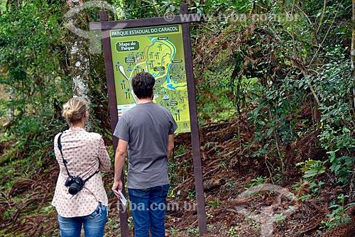 Casal de turistas consultando placa informativa com mapa do Parque Estadual do Caracol  - Canela - Rio Grande do Sul (RS) - Brasil