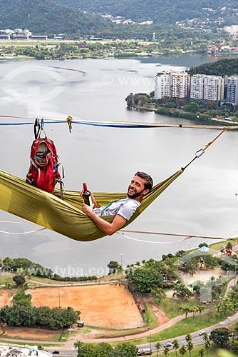 Homem deitado na rede em fita de slackline com uma garrafa de vinho no Morro do Cantagalo com a Lagoa Rodrigo de Freitas ao fundo  - Rio de Janeiro - Rio de Janeiro (RJ) - Brasil