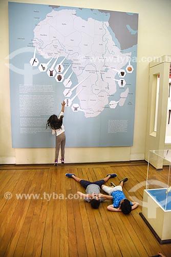 Menina interagindo com exposição África - passado e presente - em exibição no Museu Nacional - antigo Paço de São Cristóvão  - Rio de Janeiro - Rio de Janeiro (RJ) - Brasil