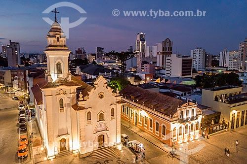 Foto feita com drone da Igreja de Nossa Senhora do Rosário de São Benedito (1946) durante o anoitecer com prédios do centro de Curitiba ao fundo  - Curitiba - Paraná (PR) - Brasil
