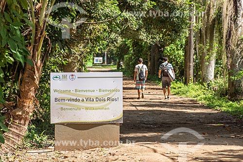 Placa com os dizeres: Bem vindo a Vila de Dois Rios com jovens ao fundo andando na estrada de terra  - Angra dos Reis - Rio de Janeiro (RJ) - Brasil
