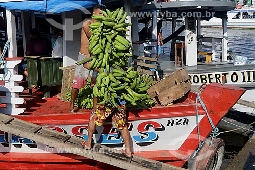 Homem carregando cachos de banana na cabeça no Porto de Manaus Moderna  - Manaus - Amazonas (AM) - Brasil
